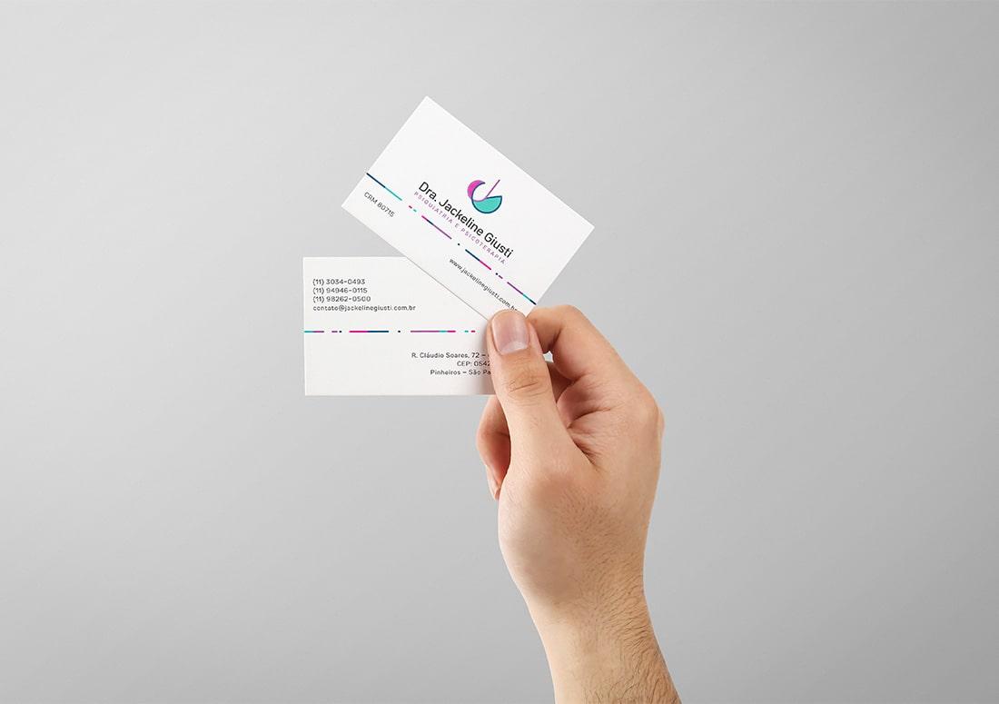 Imagem de mão segurando dois cartões de visita