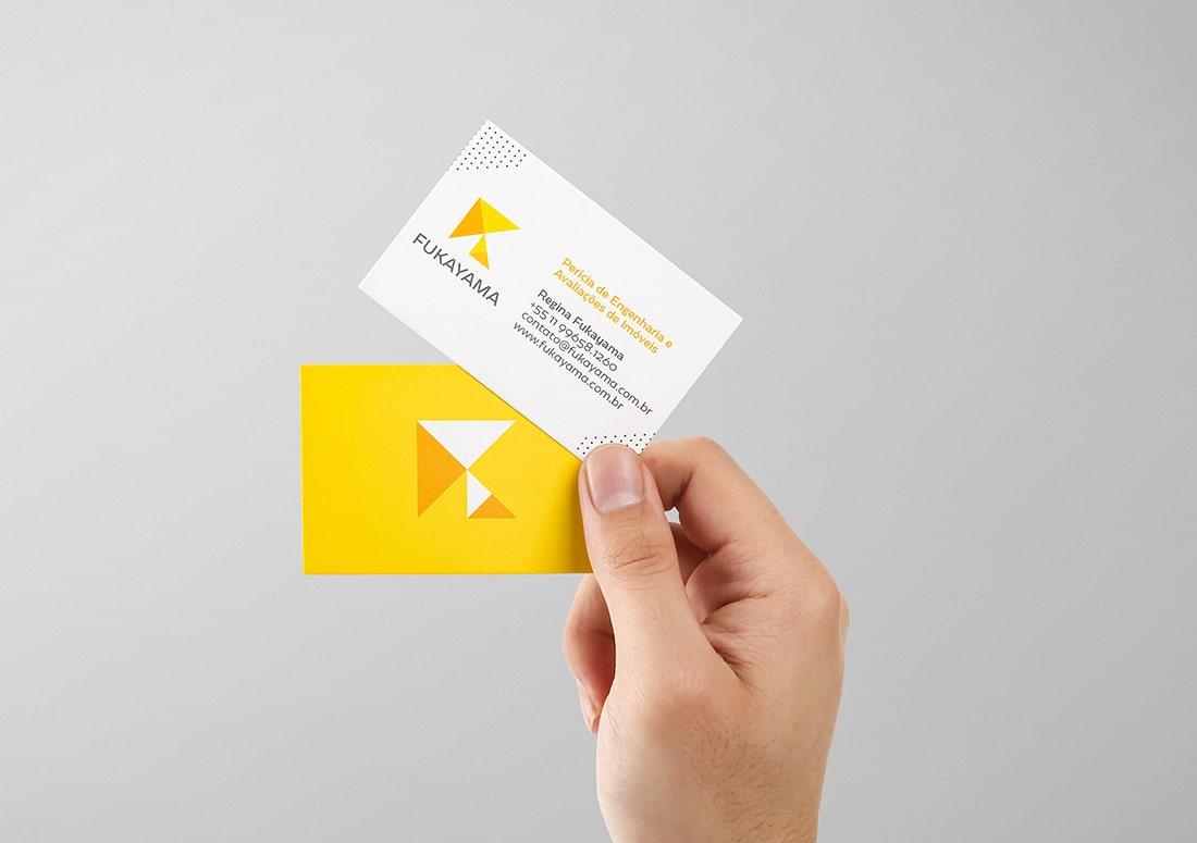 Imagem de uma mão segurando dois cartões de visita