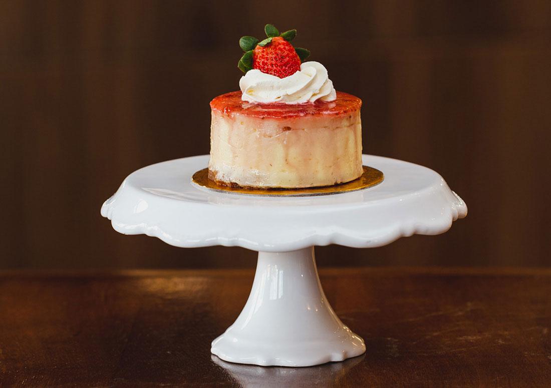 imagem de um mini cheescake de morango sobre pratinho alto