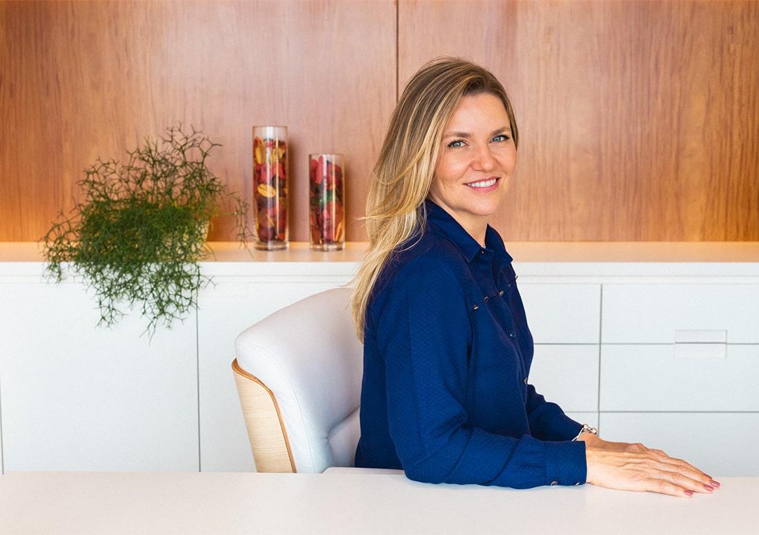 retrato Dra Jackeline Giusti sentada em sua mesa sorrindo