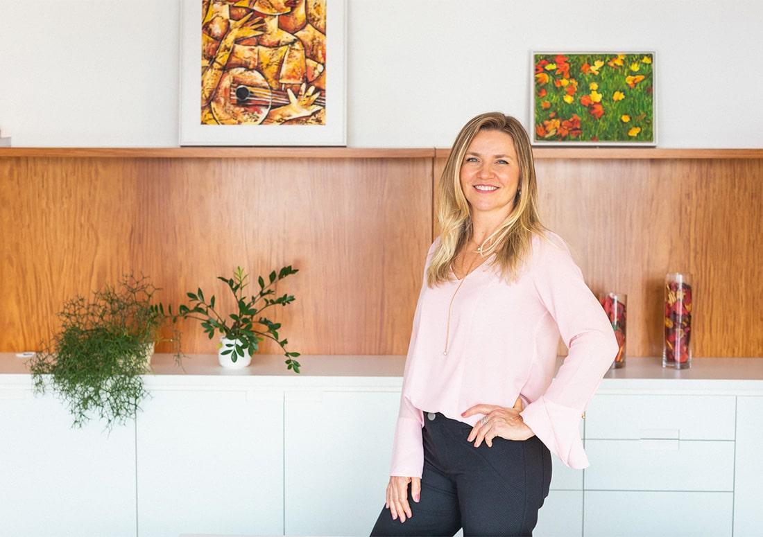 retrato profissional da Dra Jackeline Giusti em pé, sorrindo
