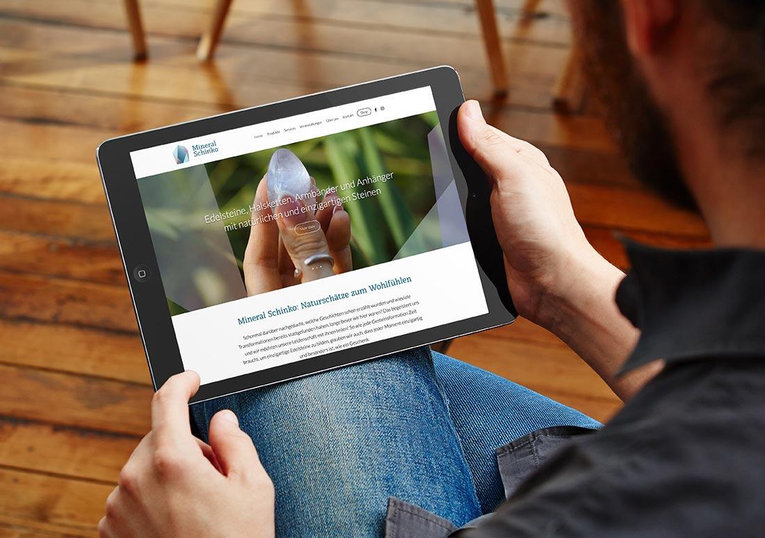 imagem de uma pessoa segurando um tablet com o site da Minera Schinko